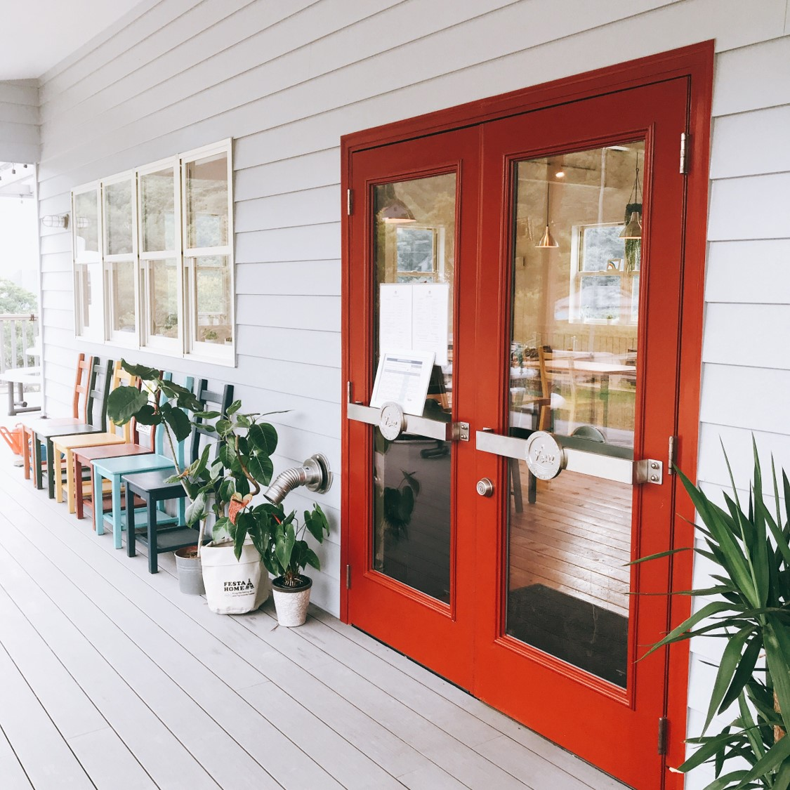 Ven店頭の写真。赤いドアの横に置かれたカラフルな椅子が特徴。