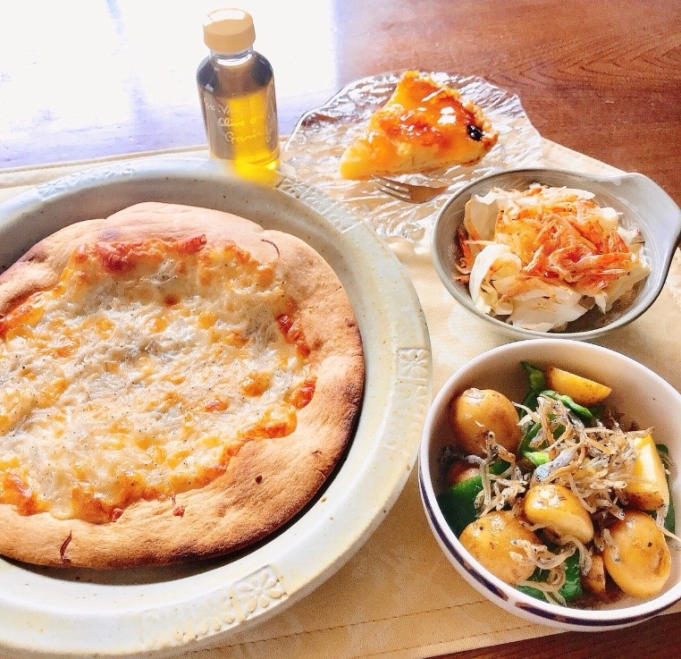 持ち帰ったお土産で作ったごはん。しらすのピザ、桜エビのサラダ、ちりめんとジャガイモの炒め物、ガーリックオイルがけ