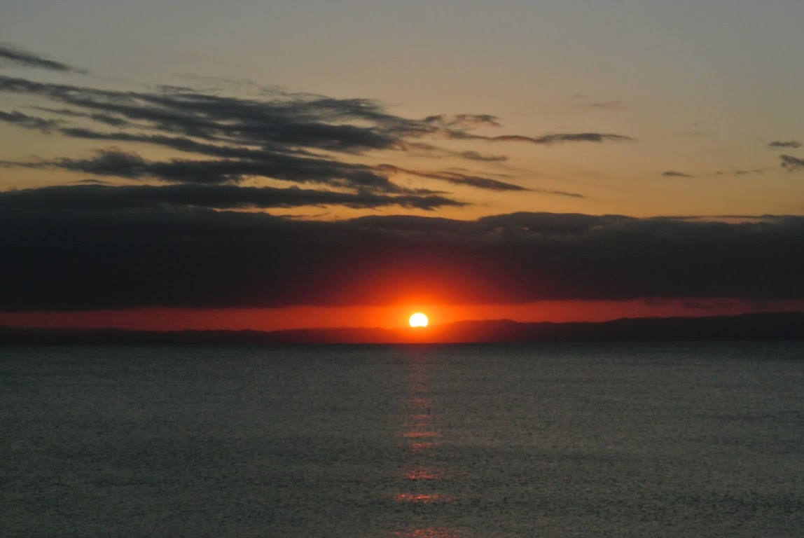 葉山の夕日と地平線。太陽が赤く輝いている。