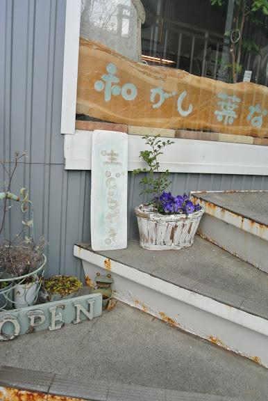 店名がかかれた木のプレートが窓の中に見える。窓の外には「生どらやき」のプレートが立てかけられ、横にはきれいなお花が飾られている。