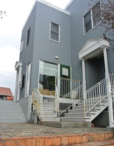 葉なの外観。階段を上った先に、緑のドア。窓辺には白いカフェカーテンが見える。