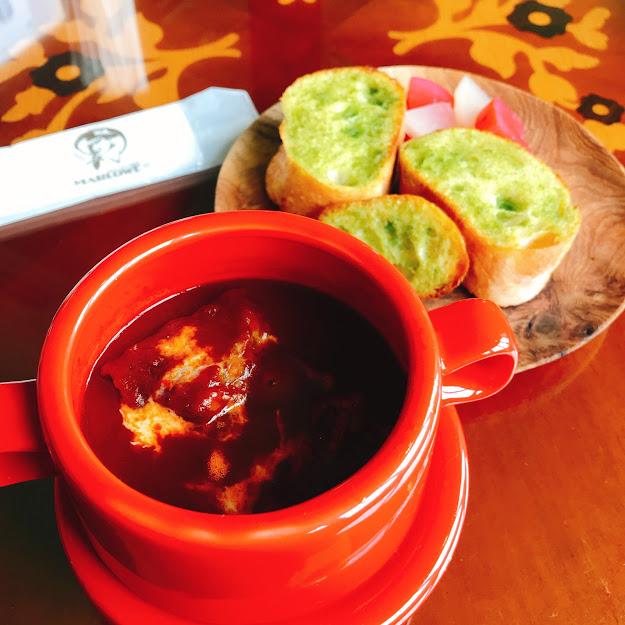 マーロウのビーフシチュー。赤い陶器の器で登場。ガーリックトーストはパセリのグリーンが映えて鮮やか。