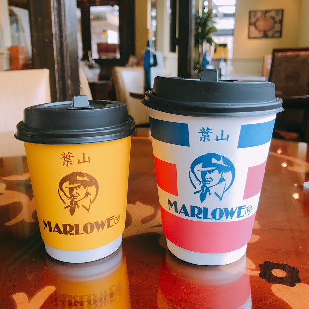 マーロウのテイクアウトカップ。Sサイズは黄色い背景に男性のイラストがプリントされている。Mサイズはピンク・白・青のトリコロールカラーで、真ん中に男性のイラストがプリントされている。