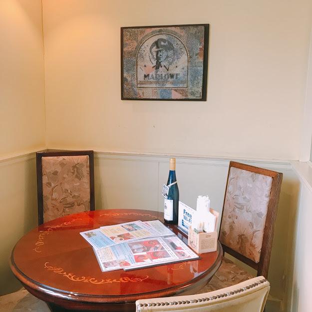 木製の丸テーブルにチェア。壁にはマーロウんの男性の絵が飾られており、大人っぽい空間。