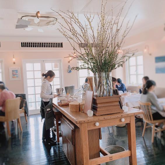 ラ・マーレの2階。中央には大きな木のテーブルがあり、カトラリーや、大きな花瓶の中に植物が飾られている。その周りには白いテーブルクロスが敷かれたテーブルが並び、お客さんがランチを楽しんでいる。