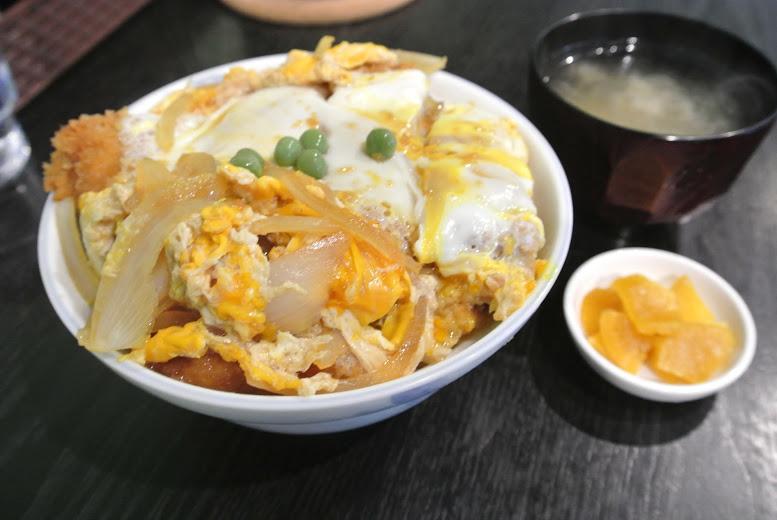 カツ丼とワカメの味噌汁と沢庵。黄色い卵でとじられたカツ丼の上には緑のグリーンピースが乗っていて、とても鮮やか。