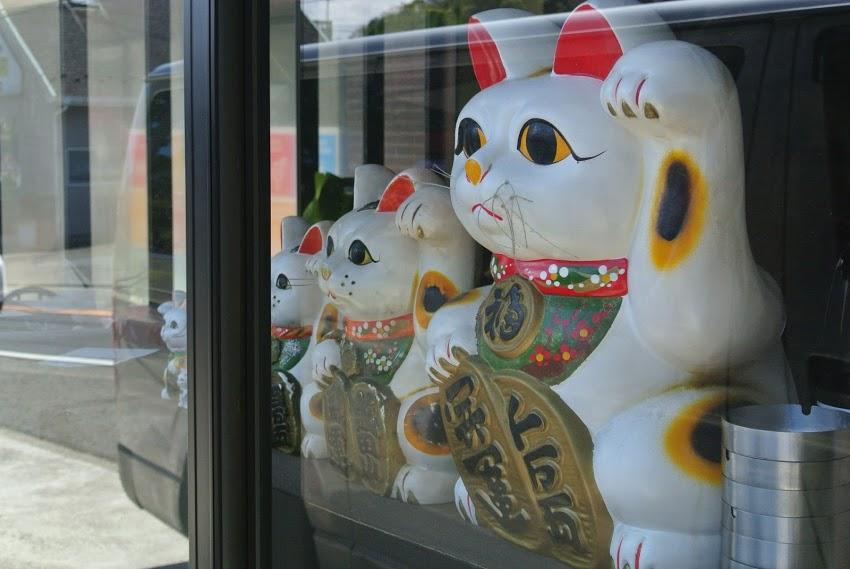 窓際の左から右へ、小さい招き猫から大きな招き猫へと、右手に小判を持った招き猫が並んでいる。