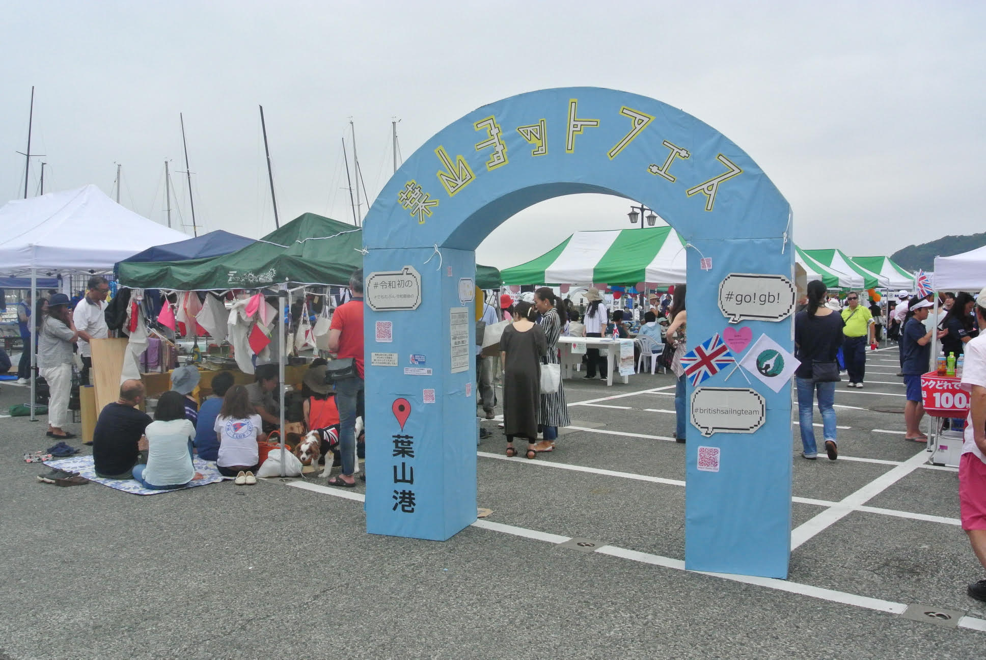 葉山ヨットフェス入口。おそらく手作りで作られた紙製の水色のアーケードには、Instagram投稿用のタグやフラッグアイテムが置かれている。