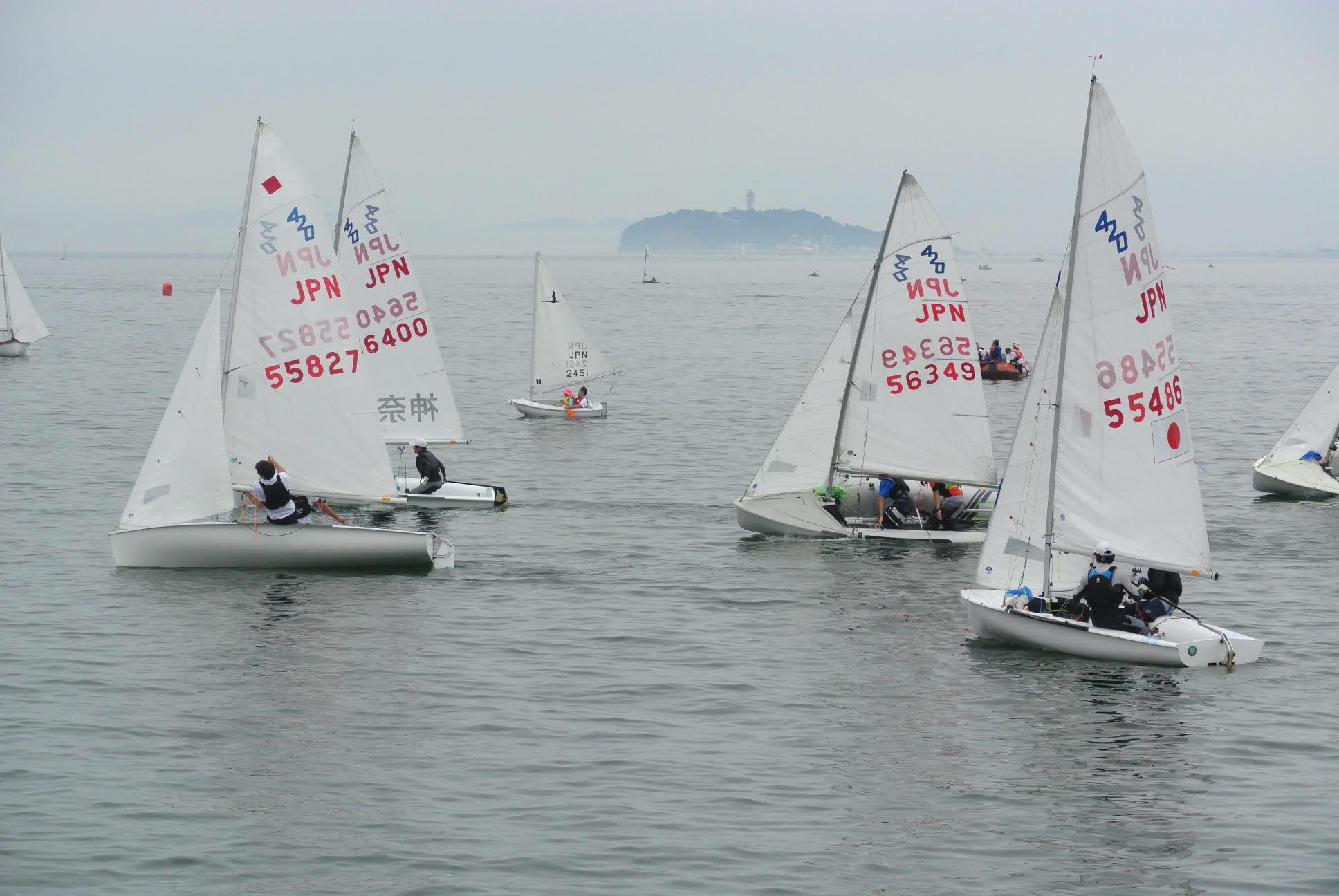 ヨットレース中。海にはたくさんのヨットが並び、競い合っている。