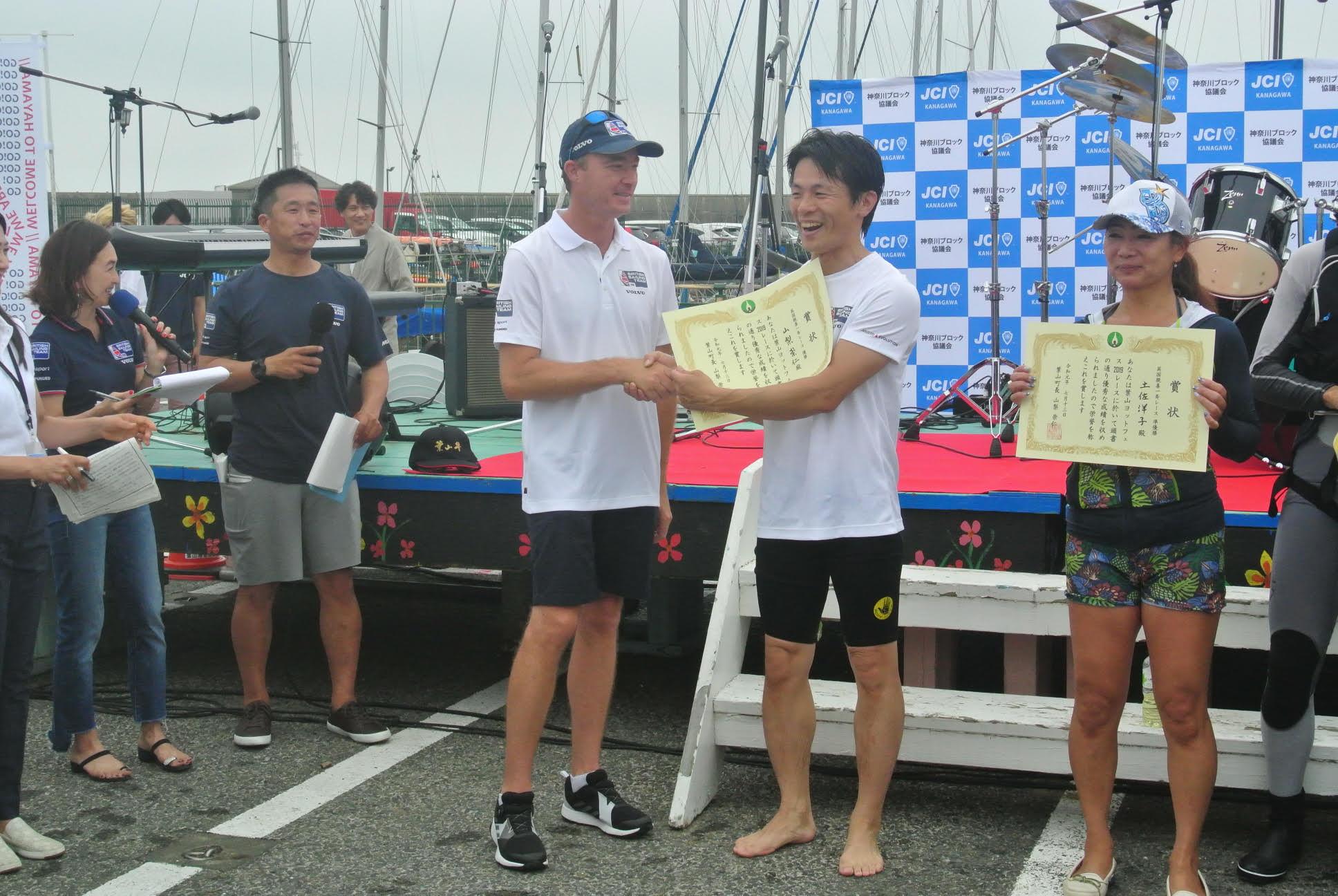 ヨットレース表彰式。市長が優勝し、手を上げて表彰状を掲げている。