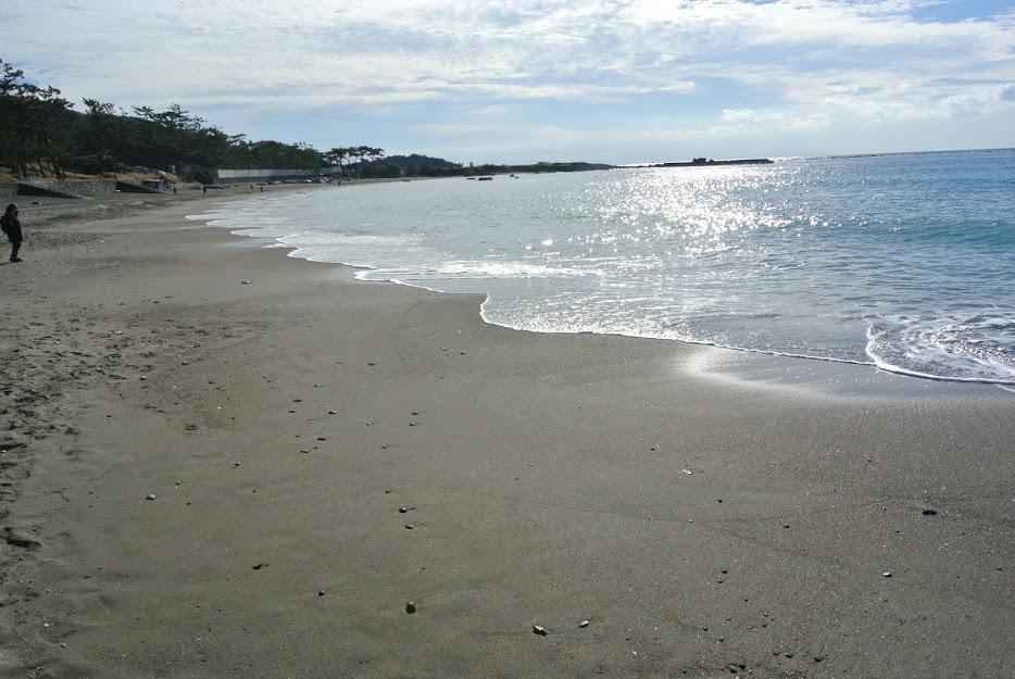朝の大浜海岸。波がキラキラ光り、足跡の少ない砂浜が広がる。