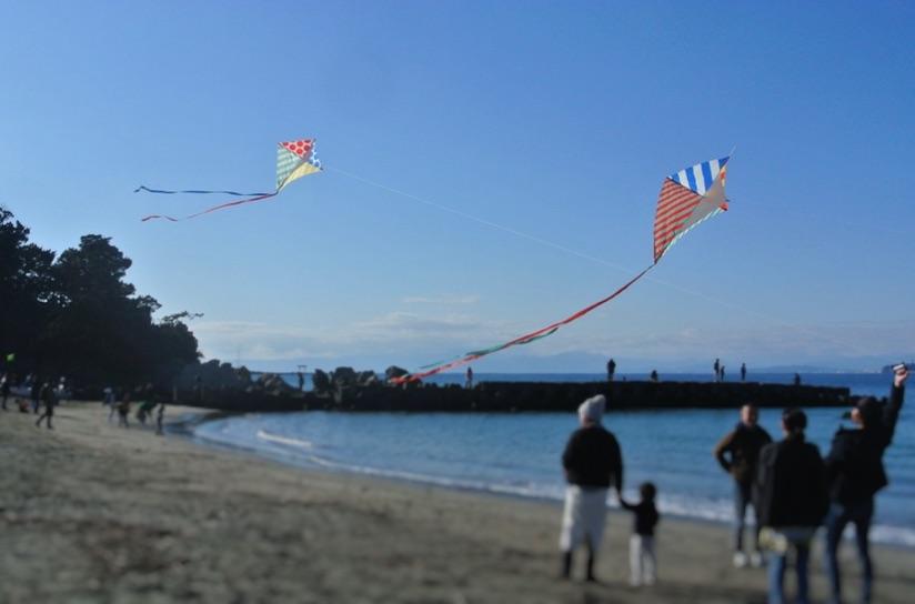 森戸海岸では子供たちが凧揚げをしている。ダイヤ型の凧が2枚上がっている。