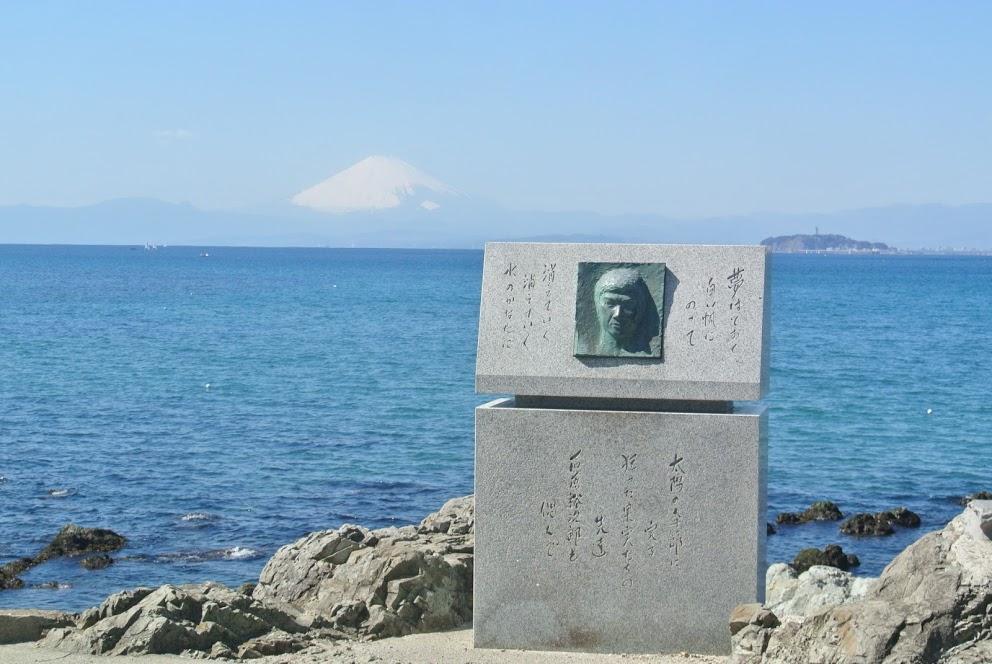 岩場にたてられた裕次郎碑。裕次郎の顔が刻まれている。後ろには青い海と富士山がみえる。
