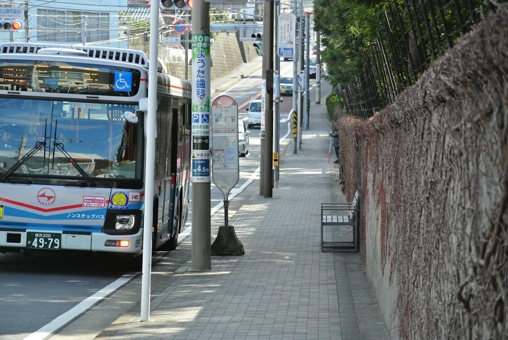 御用邸石塀。バス停「葉山」には青いバスが停車している