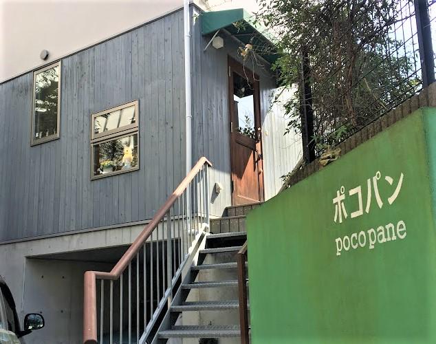 緑色の壁にポコパンの文字が見える。奥には一軒家風の黒壁の家があり、階段を上ると入口がある。