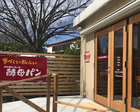 アップルの外観。壁や扉の枠の色はナチュラルブラウンで優しい印象。お店の横の木の壁には赤い大きな看板が。手作りの美味しい酵母パンと書かれている。