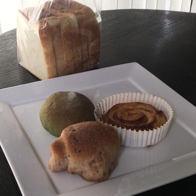 バターロール、緑の丸いパン、渦巻きのパンが白いお皿に並ぶ。場所はThe Canvas Hayama Park