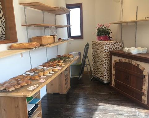 アップルの店内。写真左には長い木のテーブルに、パンがずらりと並んでいる。写真右には窯が見える。