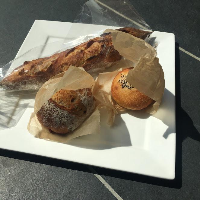 conayaのパン。バケット、アンパン、カンパーニュが白いお皿に並ぶ。場所はThe Canvas Hayama Park