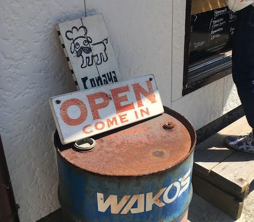 青いドラム缶の上に、ロゴのワンちゃんが書かれた木の板、OPEN COME INと書かれた板がならぶ