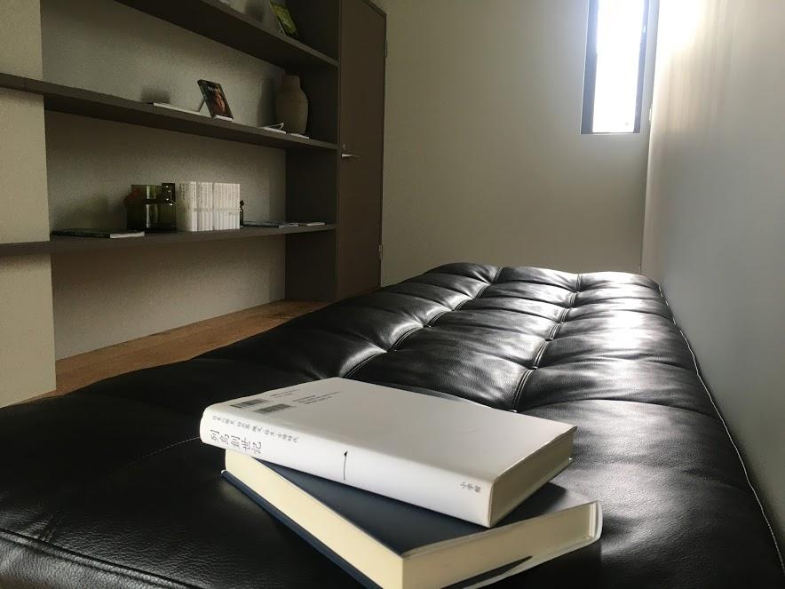 雲海のヴィラ2階にはライブラリースペースがあり、本棚にはオーナーが選書した本が並び、手前の黒い皮のソファでゆったり読書を楽しめる。