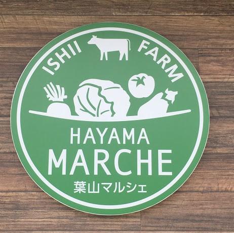 間山マルシェのロゴ。緑色の丸いロゴ。上半分には牛や野菜のデザインが、下半分には英語で葉山マルシェと書かれている。