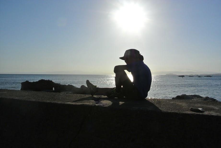 防波堤の上に少年が一人座っている。逆光で輪郭だけが黒く映り、幻想的な1枚。