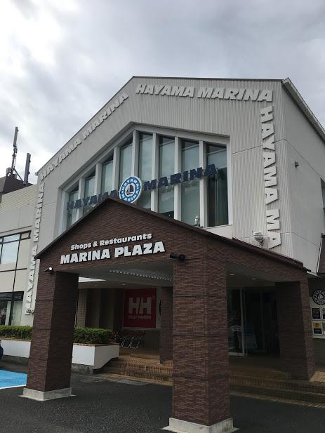 葉山マリーナの外観。三角屋根の建物にはHAYAMA MAHAYAMA MARINAのロゴが見える