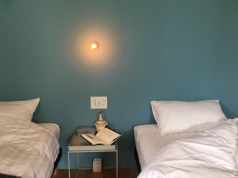 The Canvas Hayama ParkのUnkai(雲海)のベットルーム。ターコイズブルーの壁を背景に、シングルベッドが2つ並ぶ。