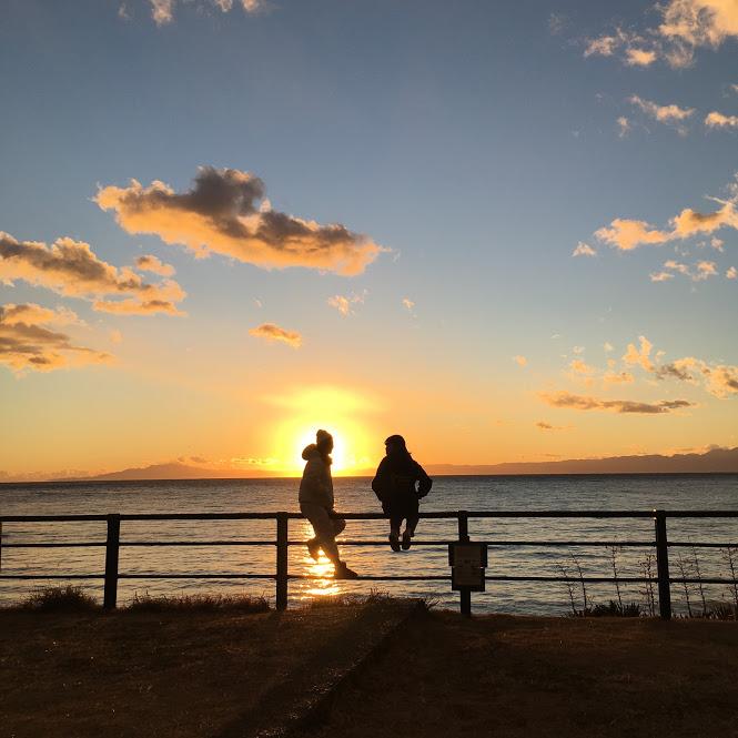 葉山公園・大浜海岸の夕日。公園の柵に腰掛ける若者2人の影が逆光となっている。