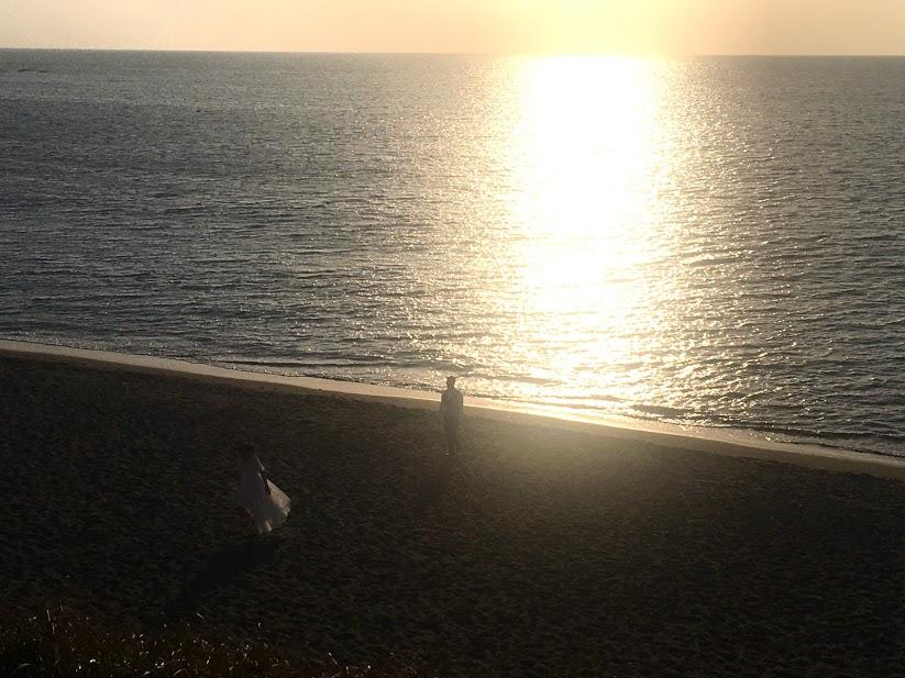 大浜海岸の夜明け。朝焼けの浜にカップルの影が見える