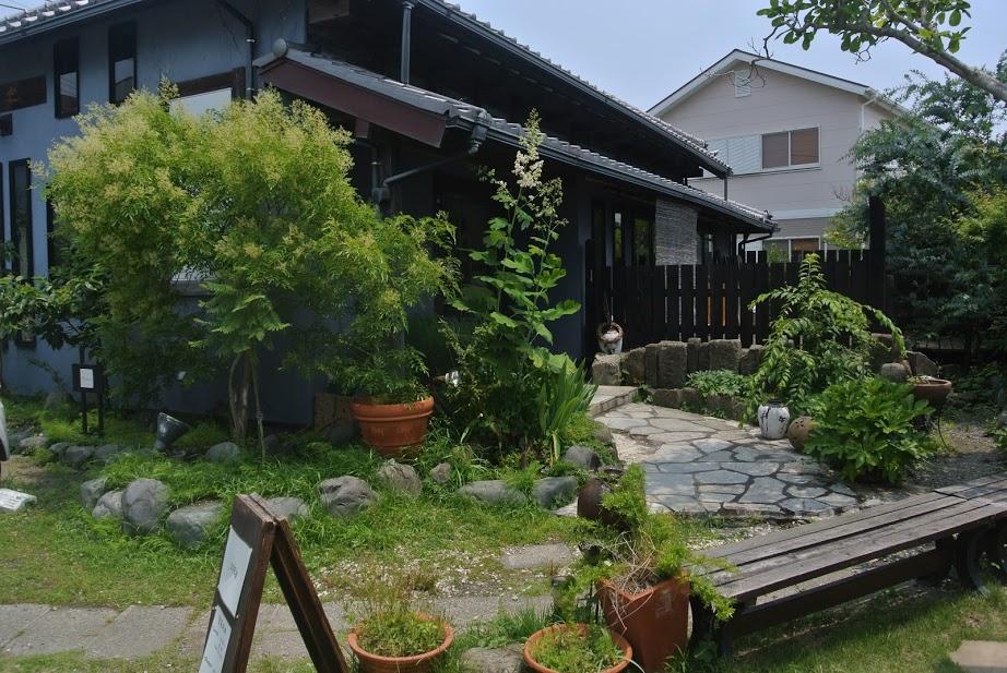 和楽の外観。緑が生い茂る庭の奥に、古民家調のお店が佇んでいる。