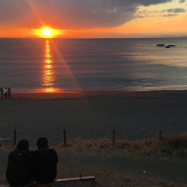 大浜海岸から見る夕日。奥紅色に光る夕日を、ベンチに座って眺めるカップルの後ろ姿が見える。