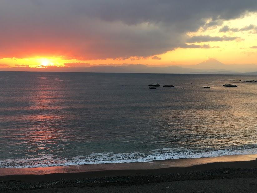 大浜海岸の夕景。地平線の左側には紅く輝くサンセット、右側には富士山のシルエットが見える
