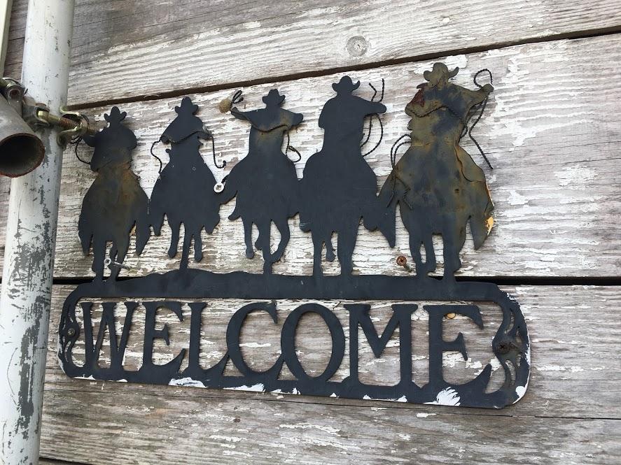 葉山まみあな牧場のプレート。5人のカウボーイのシルエットが描かれたウェルカムプレート。